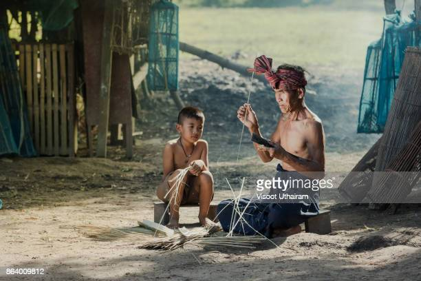 farmer with son  are weave bamboo at countryside - bamboo instrument stock photos and pictures