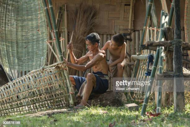 farmer with son are weave bamboo at countryside. - bamboo instrument stock photos and pictures