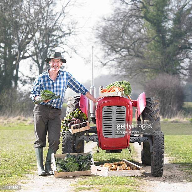 farmer with vintage tractor and vegetables.