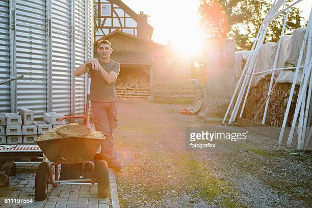 Farmer with wheelbarrow stands on his farm next to silo