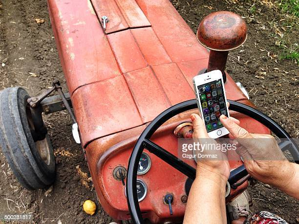 Farmer woman checking her smartphone on a tractor