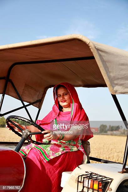 Farmer woman driving an old tractor through a field