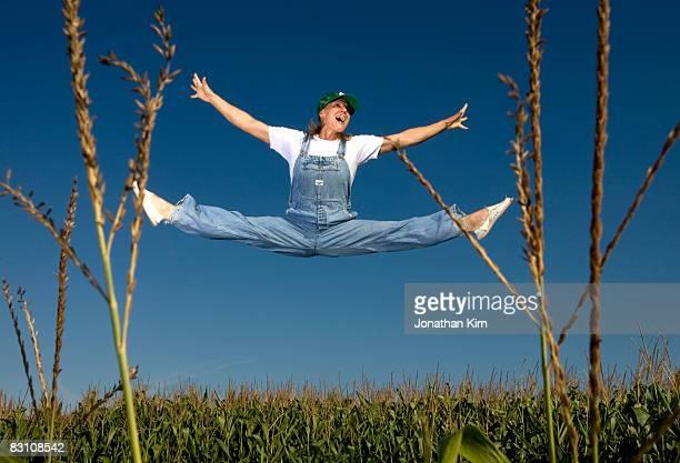 farmer woman leaps for joy over a field of corn.  - 足を開く ストックフォトと画像