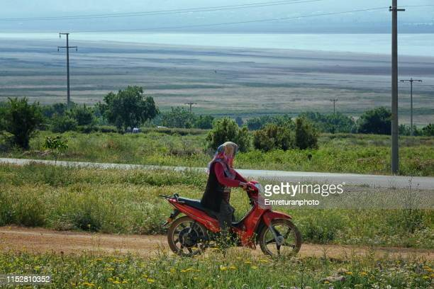 farmer woman riding a bike in the fields,i̇sparta province. - emreturanphoto stock pictures, royalty-free photos & images