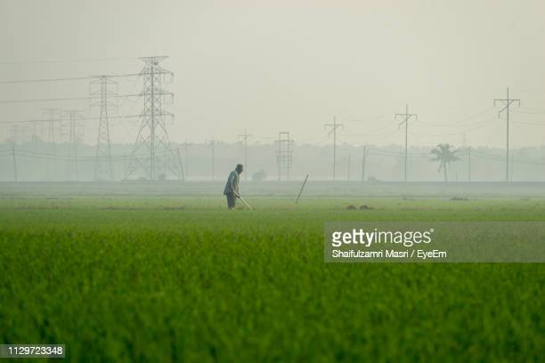 Farmer Working In Farm Against Electricity Pylons At Morning