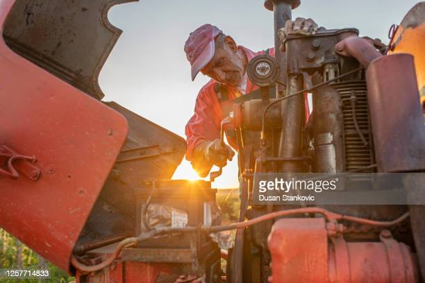 farmer working on agricultural equipment on a farm - agricultural machinery stock pictures, royalty-free photos & images