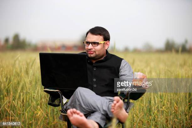 Farmer working on the laptop in the nature