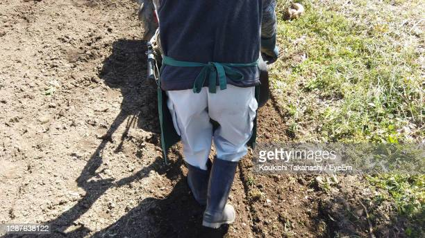 farmer working with cultivator in the farm - agriculture field - koukichi stock pictures, royalty-free photos & images