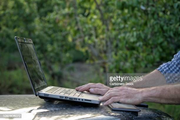 a farmer working with laptop - cena não urbana imagens e fotografias de stock