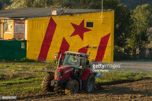 A farmer works a plot of land on a tractor next to a Catalan ProIndependence flag 'Estelada' painted on a house on September 29 2017 in Vic Spain The...