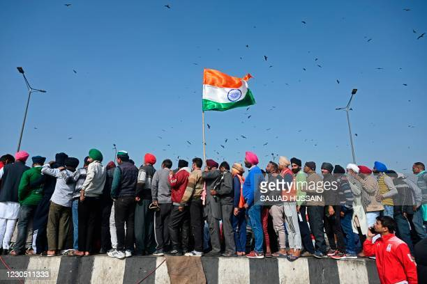 Farmers and onlookers crowd to watch a wrestling match of local wrestlers organised to show their support towards the protesting farmers against the...