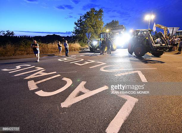 Farmers block access to the Lactalis group headquarters with a caravan of tractors as they ride over the words 'Lactalis Thieves' in Change...
