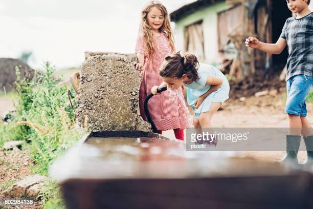 Bauernmarkt Kinder trinken von Wasser aus dem Schlauch