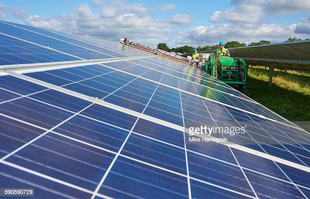 Farmers cleaning solar panels using machinery