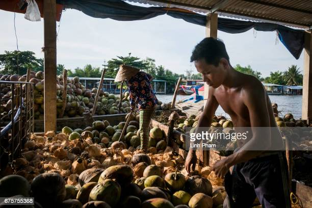Farmers cut out the mesocarp of coconuts before loading them to a boat at a floating market on April 29 2017 in An Thanh Village Mo Cay Nam District...