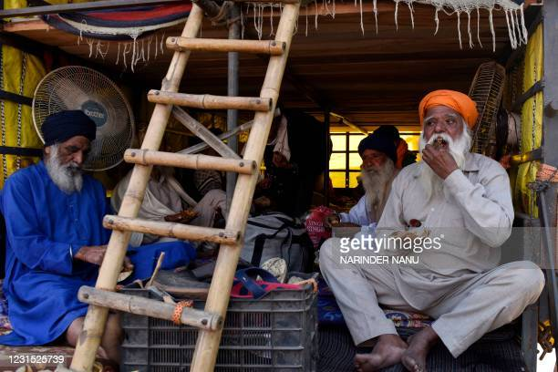 Farmers eat their meals as they take part in a demonstration and move towards Delhi to join the farmers who are continuing their protest against the...