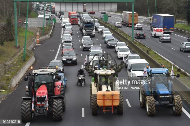 TOPSHOT Farmers from the FDSEA union drive their tractor at slow pace on January 31 2018 on the Toulouse ring road during a goslow operation...