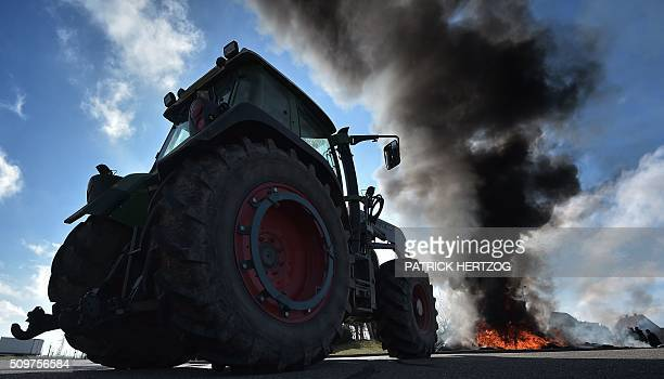 TOPSHOT Farmers from the French farmers unions burn piles of tyres in Vendenheim eastern France on February 12 protesting their increasing...