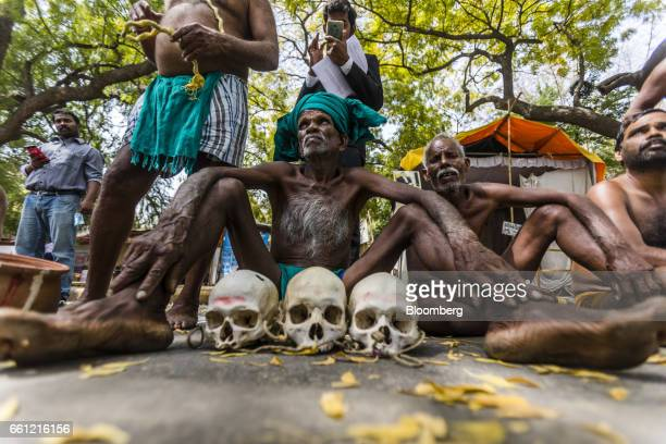 Farmers from the southern state of Tamil Nadu sit on the ground with the skulls of farmers who have committed suicide in their region during a...
