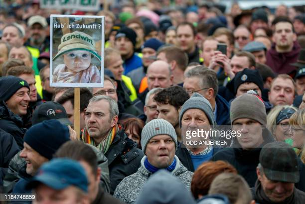 """Farmers gather near Brandenburg Gate with a photo of a baby bearing the inscription """"Do I have a future?"""" during a protest on November 26, 2019 in..."""
