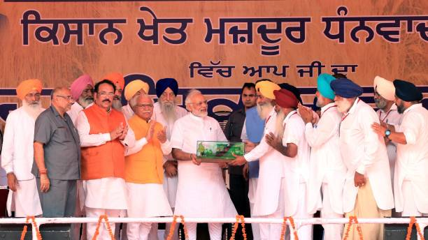 Farmers give memento Prime Minister Narendra Modi during `thanksgiving` rally of farmers at Malout in Muktsar on July 11 2018 near Bhatinda India...