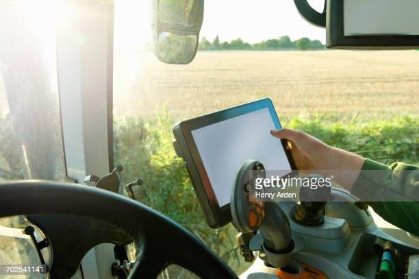 Farmers hand driving tractor using touchscreen on global positioning system