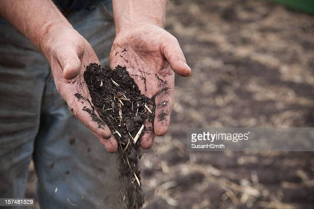 Farmer's hands holding soil.