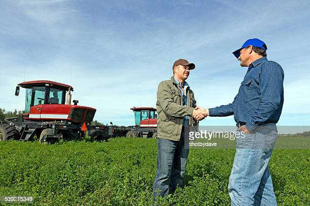farmers handshake at a farm with tractors - farmer stock pictures, royalty-free photos & images