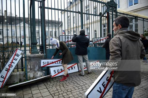 Farmers hanging town boundary signs on the facade of the Prefecture take part in a demonstration to protest against the PAC on February 12 2018 in...