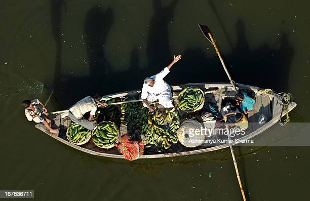 Farmers head to markets with their summer vegetable on a Boat in River Ganges, for selling them at market in Allahabad,Uttar Pradesh, India on...