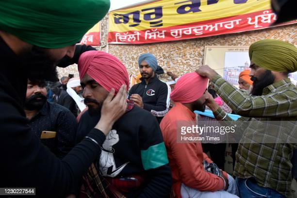 Farmers help each other with their turbans at Singhu border during the ongoing protest against new farm laws, on December 19, 2020 in New Delhi,...