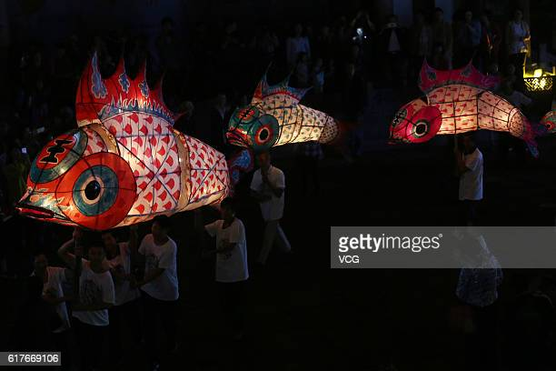 Farmers holding fishshaped lanterns parade during a local festival to pray for good harvest at Liyang old street on October 23 2016 in Huangshan China