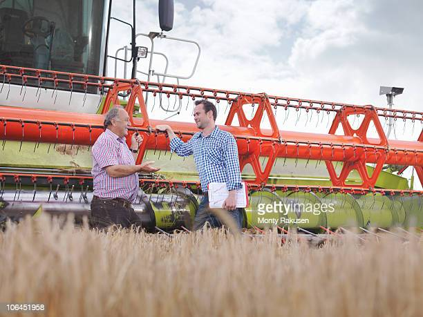 Farmers in front of combine harvester