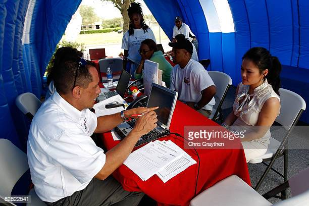 Farmer's Insurance agent Jim Baney helps Pasadena resident Tuyet Pham process her claim after suffering damage from Hurricane Ike September 15, 2008...
