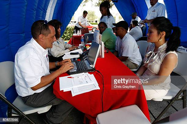 Farmer's Insurance agent Jim Baney helps Pasadena resident Tuyet Pham process her claim after suffering damage from Hurricane Ike September 15 2008...