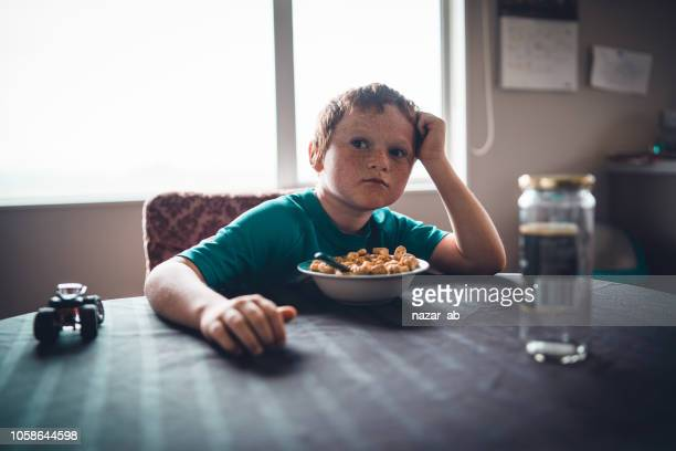 Farmers kid on table with cornflakes in bowl.