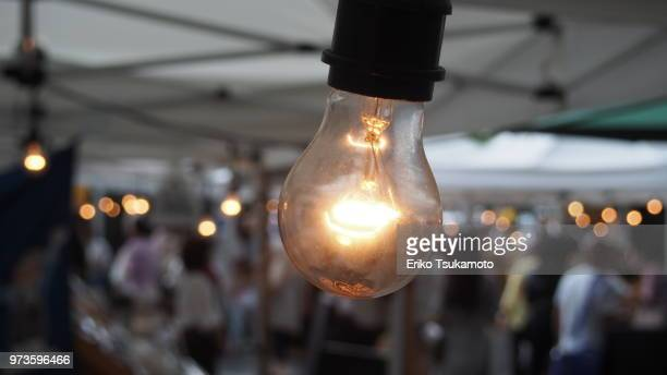 Farmer's Market nakid light bulb and blurred crowd of people