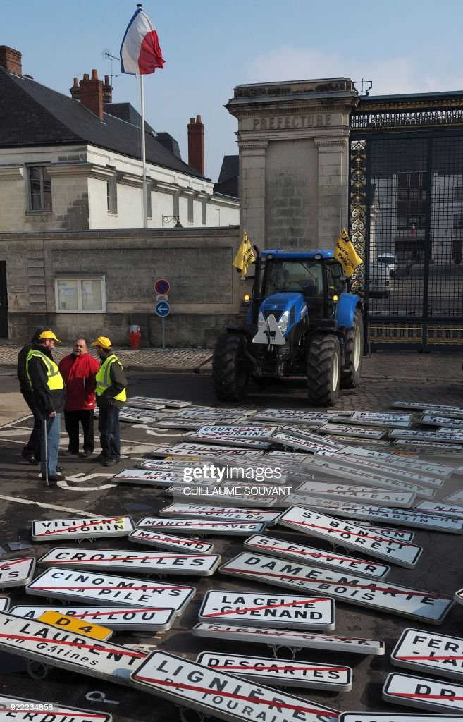 Farmers of the Coordination Rurale (CR) 37 agricultural union put town boundary signs on the ground in front of the prefecture and block the entrance with tractors as part of a demonstration to protest against the Common Agricultural Policy (PAC) in Tours, centre-west France, on February 21, 2018. /