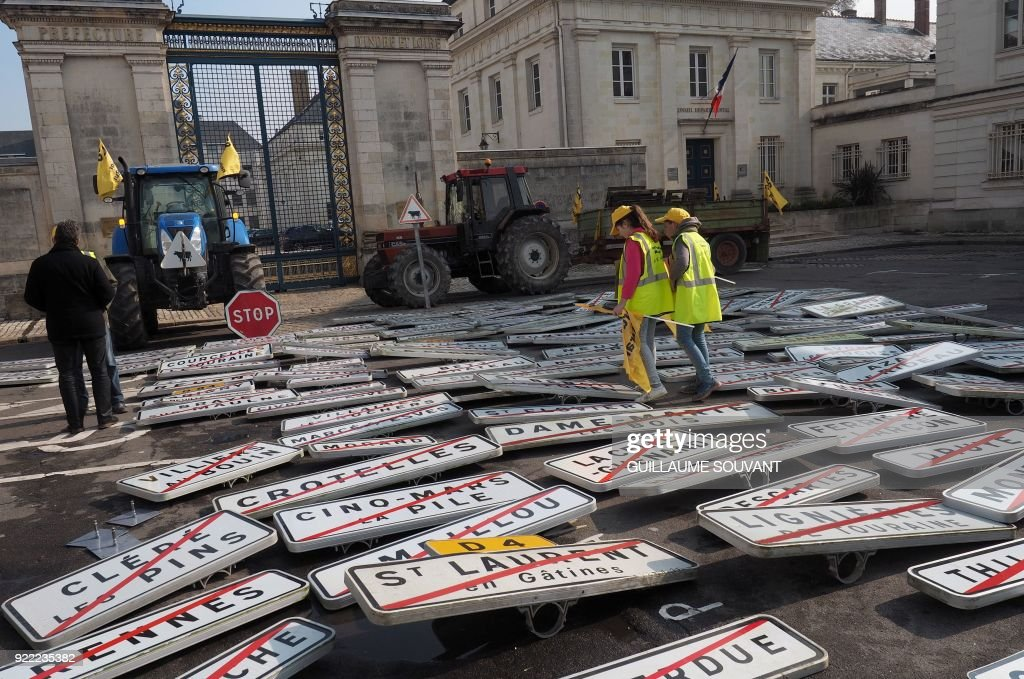 Farmers of the Coordination Rurale (CR) 37 agricultural union put town boundary signs on the ground in front of the prefecture as part of a demonstration to protest against the Common Agricultural Policy (PAC) in Tours, centre-west France, on February 21, 2018. /