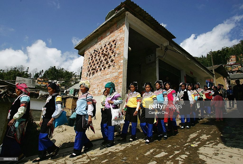 Farmers of the Yi ethnic group attend a ceremony at the dragon festival on February 12, 2006 in Yuanyang County, Yunnan Province, China. During the festival, the Yi people get together to worship water, the dragon and heaven in expectations of a bumper grain harvest and favorable weather for the coming year. At the banquet, each household contributes to the preparation of Yi style chicken, fish, and minced pork dishes. These are placed on a 700-meter-long chain of tables from each household in the main street.
