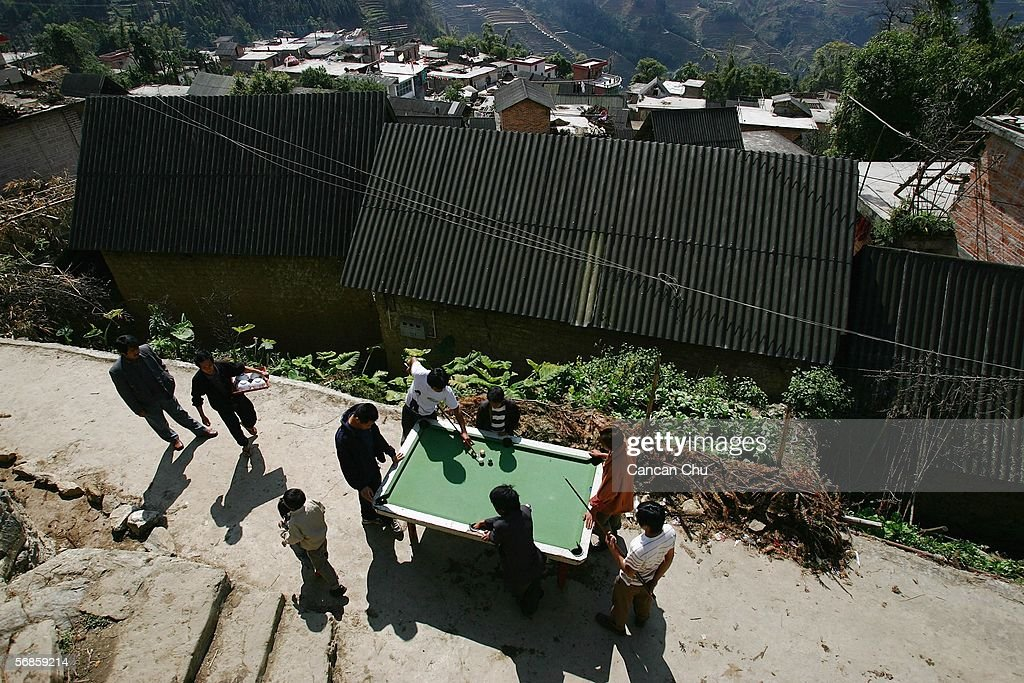 Farmers of the Yi ethnic group play billiards on February 12, 2006 in Yuanyang County, Yunnan Province, China. Yuanyang County is world famous for its Hani and Yi, ethnic minority-constructed farming terraces, that zigzag upwards over range upon range of slopes from heights of 144 to 2,000 meters.