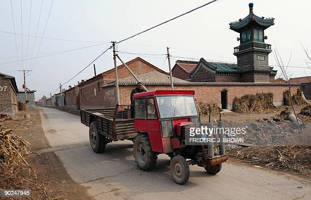 Farmers on their vehicle pass the village mosque in Niujinzhuang in Mencun County on February 25, 2009 in northern China's Hebei province. The Hui...