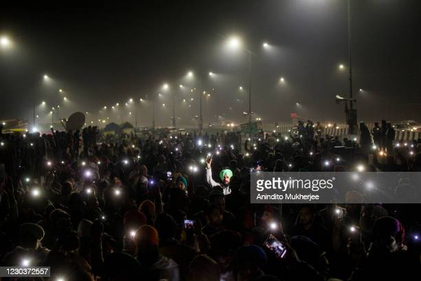 Farmers raise their phones with the torches on as they participate in a vigil on New Year's Eve remembering the 40 farmers who lost their lives...