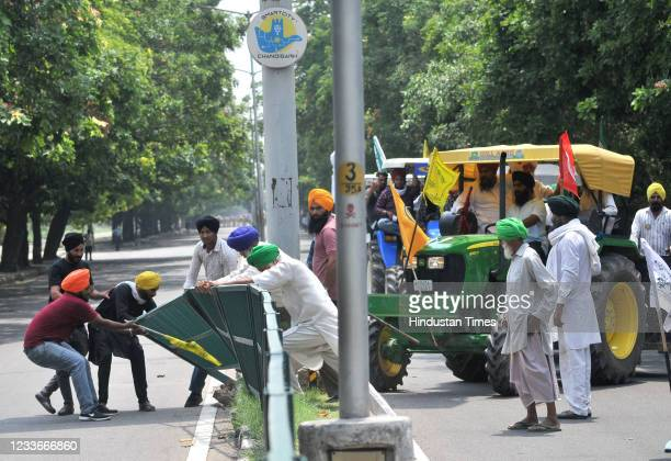 Farmers remove a road dividing fence while marching towards Punjab Raj Bhawan to mark seven months of farmers agitation against the three new farm...