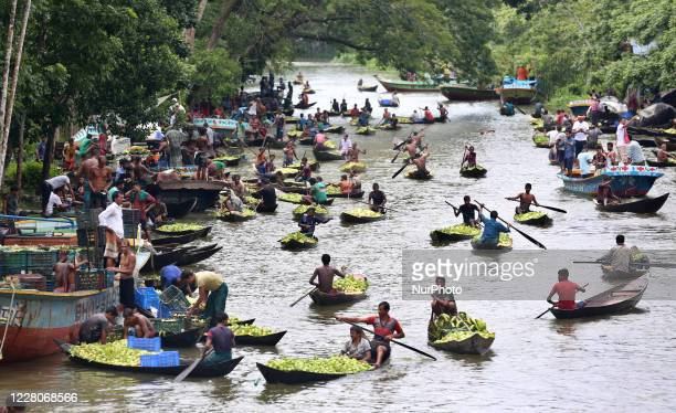 Farmers row boats loaded with guavas on their way to a floating market in Barisal, Bangladesh on August 16, 2020. Thousands of farmers earn their...