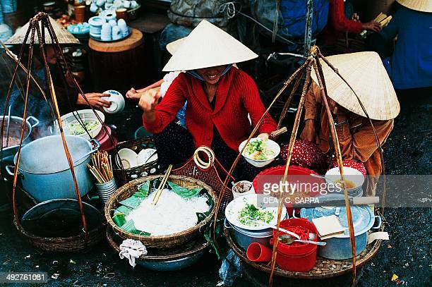 Farmers selling food on the street market in Hanoi Vietnam