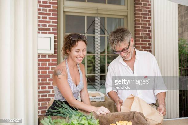 farmers selling organic vegetables on stall outside store - heshphoto stock pictures, royalty-free photos & images
