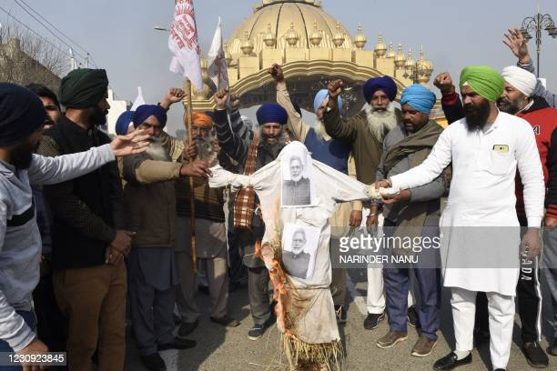 Farmers shout slogans as they burn an effigy of Indian Prime Minister Narendra Modi during a protest against the central government's recent...