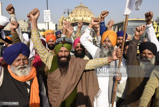 Farmers shout slogans as they take part in a demonstration and move towards Delhi to join the farmers who are continuing their protest against the...