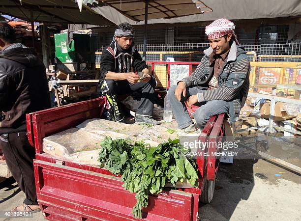 Farmers sit in the back of their van as they sell their vegtables in the center of the city of Fallujah west of the capital Baghdad on January 8...